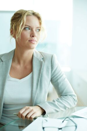 Portrait of pensive businesswoman in eyeglasses working in office photo