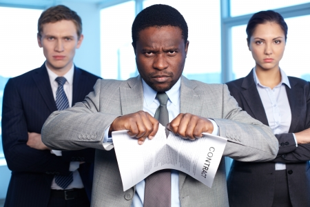 Portrait of African businessman tearing contract while looking at camera with two partners near by photo