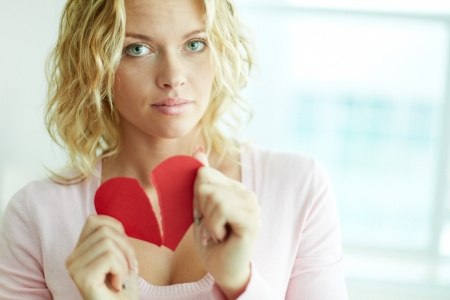 lonely heart: Sad female tearing up red broken paper heart Stock Photo