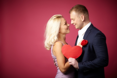 Two young dates looking at one another with paper heart between them Stock Photo - 16611395