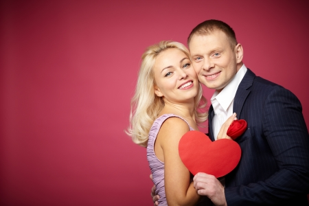 Portrait of elegant happy couple with red paper heart looking at camera Stock Photo - 16611399