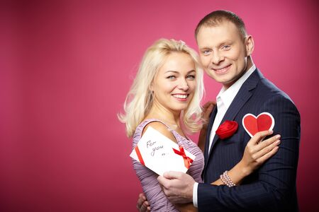 Portrait of elegant happy couple with valentine cards looking at camera Stock Photo - 16611394