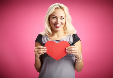 Pretty female with red paper heart looking at camera with smile photo