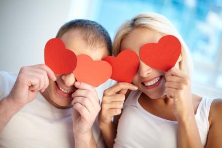 parejas jovenes: Retrato de pareja feliz celebraci�n de los corazones rojos de papel por sus ojos