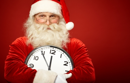 Photo of happy Santa holding clock showing five minutes to midnight photo