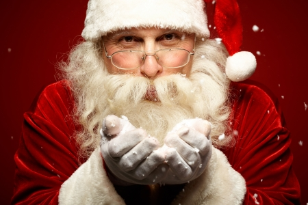 Photo of Santa Claus in eyeglasses blowing snow and looking at camera photo