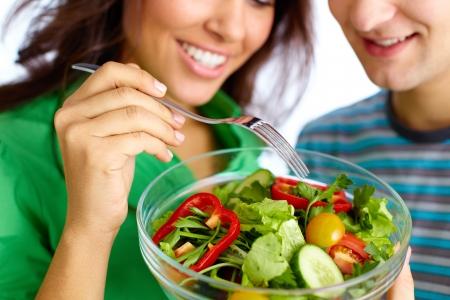 Close-up de ensalada de vegetales joven pareja comiendo de un tazón de vidrio