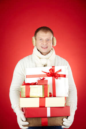 Portrait of happy man in white winterwear with stack of giftboxes looking at camera Stock Photo - 16611995