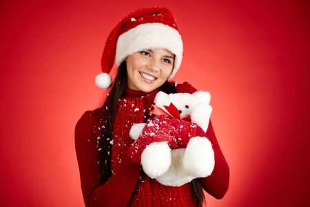 Joyful girl in Santa cap with white teddy bear over red background photo