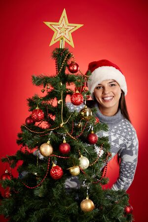 Portrait of happy girl in Santa cap looking at camera out of decorated firtree Stock Photo - 16612000