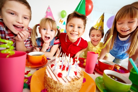 Group of adorable kids gathered around birthday cake with candles photo