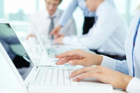 mecanografía: Primer plano de las manos femeninas escribiendo en el teclado del ordenador portátil