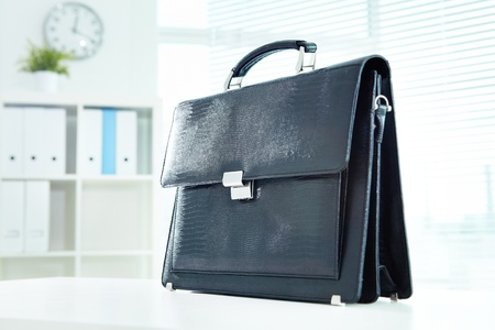 brief case: Image of black leather briefcase on desk in office