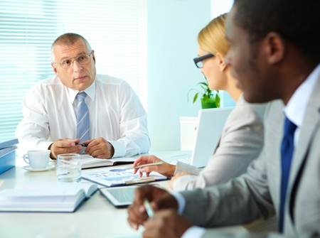 Portrait of senior boss looking at his employees at meeting Stock Photo - 16730298