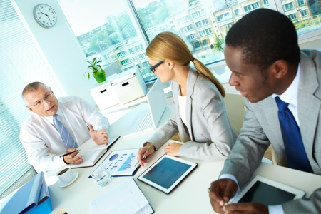 Portrait of senior boss and his employees discussing new project at meeting Stock Photo - 16730224