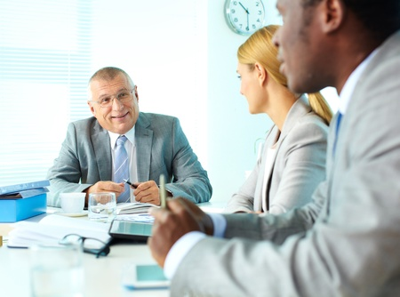 Portrait of smiling senior boss looking at his employees at meeting Stock Photo - 16730237