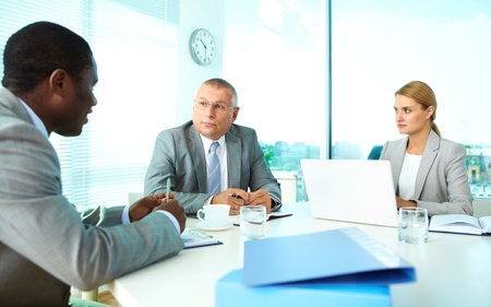 Portrait of serious boss looking at his employee with pretty secretary near by Stock Photo - 16730255