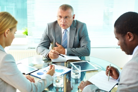 Portrait of serious boss interacting with his employees Stock Photo - 16730169