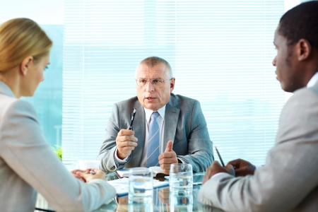 Portrait of serious boss talking to his employees Stock Photo - 16730171
