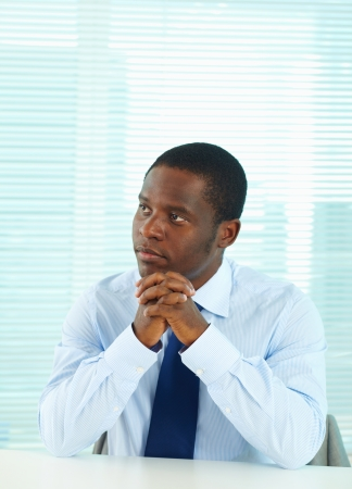 Portrait of pensive African businessman sitting in office photo