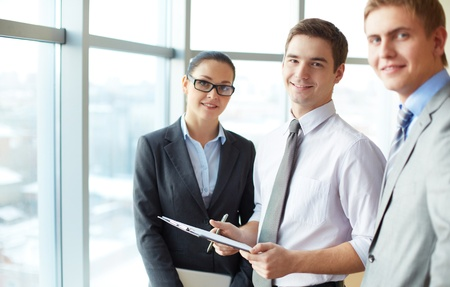 Image of three employees looking at camera, focus on elegant man with clipboard Stock Photo - 16730294