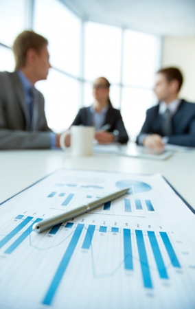 busy office: Business document on background of employees planning work at meeting Stock Photo