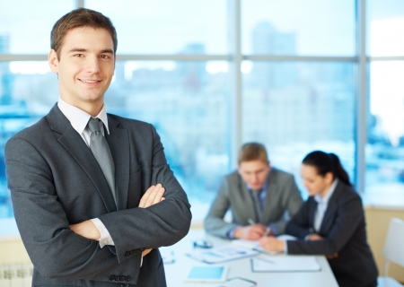 confident man: Image of cross-armed leader looking at camera in working environment