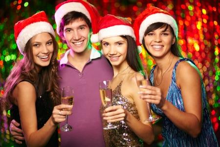 Portrait of four joyful friends toasting at xmas party photo