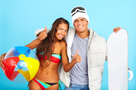 Portrait of happy girl in bikini with ball and handsome man in winterwear holding snowboard showing thumbs up and looking at camera photo
