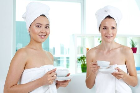 tea towel: Girls in bath towels holding cups and looking at camera in spa salon Stock Photo