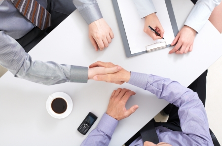 financial agreement: Above view of businessmen doing agreement at workplace