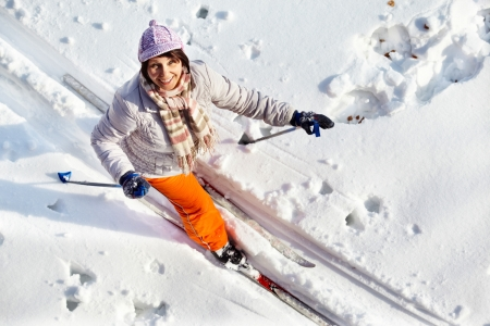 winterwear: Above angle of middle aged woman skiing outside