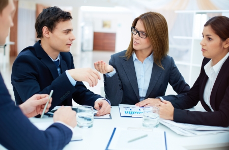 young professionals: Group of confident business partners planning work at meeting Stock Photo
