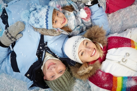 Happy parents and their daughter in winterwear lying in snow photo