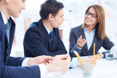 team planning: Image of confident businessman listening to his partner while looking at her at meeting Stock Photo