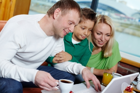 Family of three looking at the laptop screen in cafe Stock Photo - 16848898