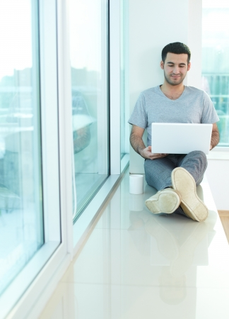 windowsill: A young guy with laptop sitting on window sill