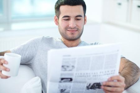 periodicos: Un hombre joven con el peri�dico que la lectura en casa Foto de archivo