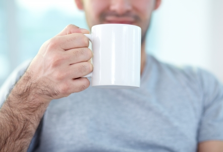 hairy arms: Close-up of male hand holding mug Stock Photo