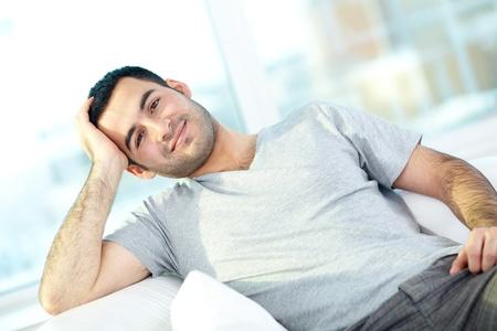hombre sentado: Un hombre joven que busca a camaera mientras se relaja en su casa Foto de archivo
