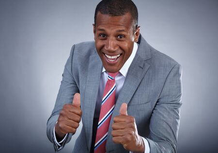 Happy businessman keeping his thumbs up with smile over grey background Stock Photo - 16848813