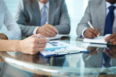 reuniones empresariales: Primer plano de la mano humana con la pluma apuntando al papel al explicar algo a los colegas Foto de archivo