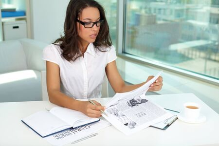 Portrait of smart businesswoman reading latest news in office photo