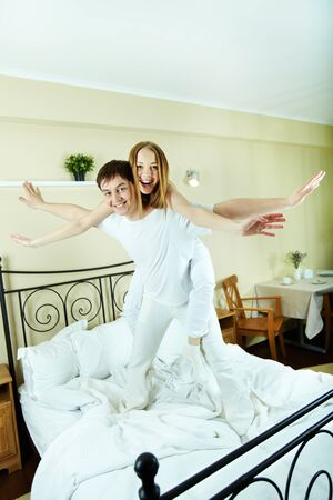 Happy girl embracing her boyfriend during piggyback in bedroom photo