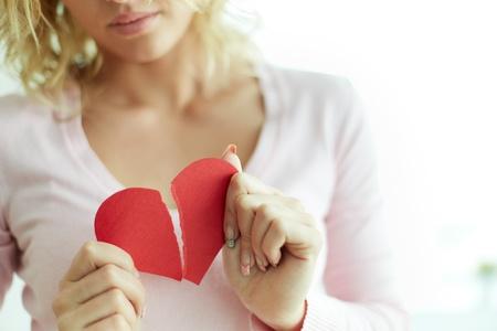 corazon roto: Primer plano de la mujer que muestra el corazón rojo de papel roto