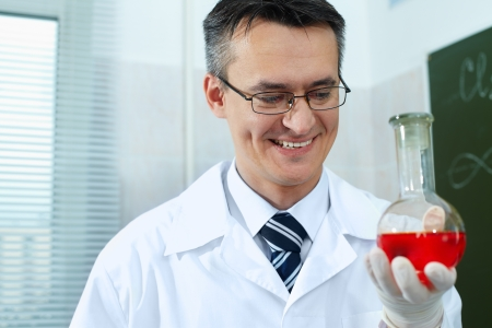 Male scientist in eyeglasses holding glassware with new substance photo