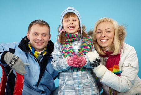 Happy parents and their daughter in winterwear looking at camera with smiles Stock Photo - 16964201