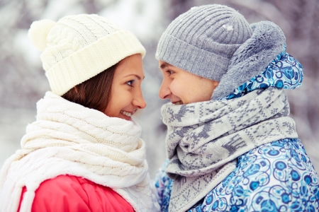 Portrait of happy young woman and her boyfriend in winterwear looking at one another  Stock Photo - 16964187