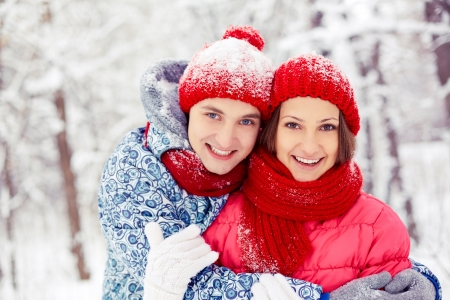 winterwear: Portrait of happy young couple looking at camera in winter park  Stock Photo