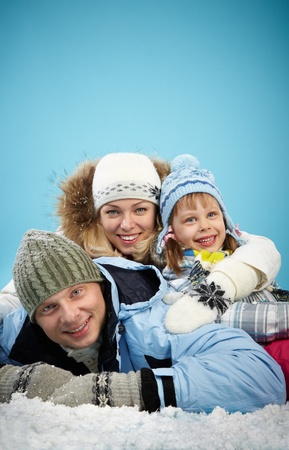 Happy parents and their daughter in winterwear lying in snow Stock Photo - 16964168